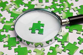 Magnifying glass on the green puzzle — Foto de Stock