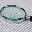 Magnifying glass on a binary code — Stock Photo #16572365