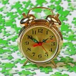 Alarm clock on the green puzzle — Stock Photo #16636245