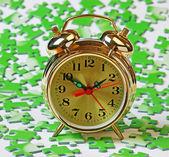 Alarm clock on the green puzzle — Stock Photo