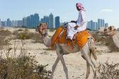 ベドウィン、horizo に近代的な都市、砂漠でのラクダ — ストック写真