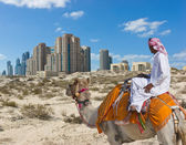 Bedouin on a camel in the desert and a modern city on the horizo — Stock Photo
