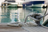 Mooring rope with a knotted end tied around a cleat on a wooden — Stock Photo