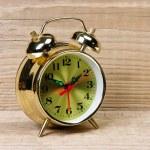 Golden alarm clock on wooden table — Stock Photo #17390999