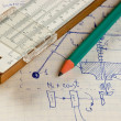 Pencil and a slide rule on the old page with the calculations in - Stock Photo