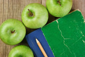 Apple and a notebook on a wooden background — Stock Photo