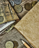Old notes and coins and pencil on a wooden table — Stock Photo