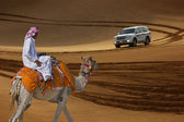 Bedouin on a camel in the desert and Jeep safari in the sand dun — Stock Photo