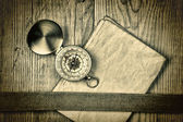 Vintage paper with compass on old wooden boards — Stock Photo