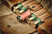 Old hunting cartridges and bandoleer on a wooden table — Stock Photo