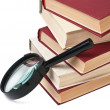 Stack of books and magnifying glass — Stock Photo #2067783