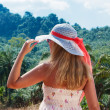 Young woman in a hat watches landscape jungle — Stock Photo