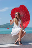 Young girl with a red umbrella sits on the waterfront and looks — Stock Photo