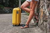 Female feet with yellow suitcase — Stock Photo