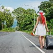 Young girl walking down the road with a suitcase — Stock Photo #21413663