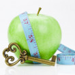 Green apple and blue measure tape with clue on white background - Photo