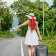 Young girl walking down the road with a suitcase — Stock Photo #21561045