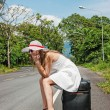 A young girl sitting on a suitcase on the road — Stock Photo #21561081