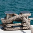 Knot on a bollard of a boat. Blue sea in a background - Lizenzfreies Foto