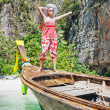 A young girl stands on Thai Longtail boat on the beach Maya Bay — Stock Photo