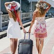 Two young girls walk along the road with a suitcase — Stock Photo #21666633