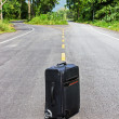 Royalty-Free Stock Photo: Lone suitcase stands in the middle of the road