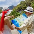Stock Photo: Womand mlooking at map on tropical landscape
