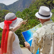 Woman and man looking at the map on a tropical landscape - Stock Photo