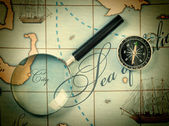 Magnifier and compass on map — Stock Photo