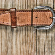 Vintage belt buckle on a old wooden board - Stock Photo