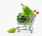 Green sweet pepper paprika in shopping trolley on white backgro — Stock Photo