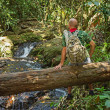 Travelling man sitting on a log near the river in the jungle - ストック写真