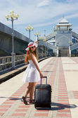 Young girl with a suitcase and smiles — Stock Photo