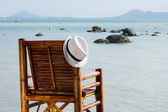 Hat on a bamboo chair on the beach — Stock Photo