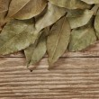 Dry bay leaf on old wooden board — Stock Photo #22405883