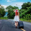 Young girl walking down the road with a suitcase — Stock Photo #22405957