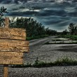 Old wooden road sign on a dark deserted road - Stock Photo