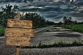 Old wooden road sign on a dark deserted road — Stock Photo