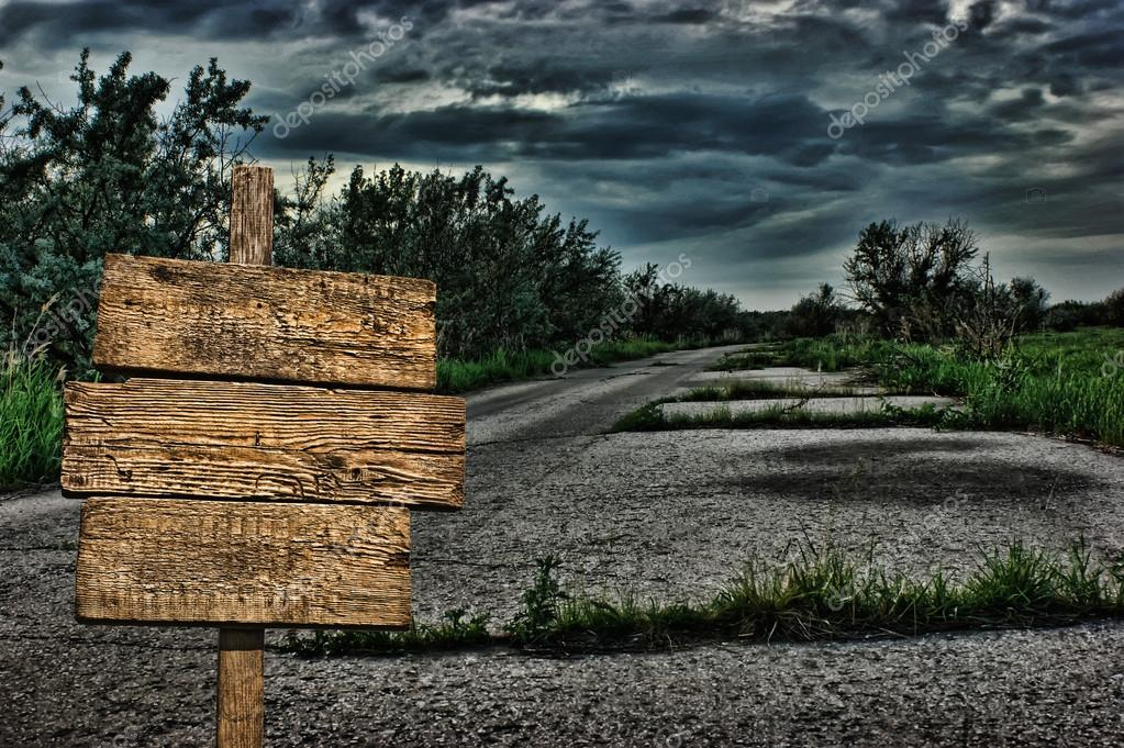 old wooden road sign on a dark deserted road � stock photo