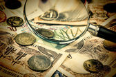 Magnifying glass on a pile of old European money — Stock Photo
