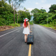 Young girl walking down the road with a suitcase — Stock Photo #22897466