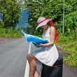 A young girl sitting on a suitcase with a map in hand — Stock Photo #22897486