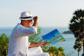 A young man in a white suit sitting on the beach with a map — Stock Photo