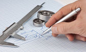 Pen in hand and technical drawing — Stock Photo