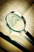 Books and magnifying glass — Stock Photo