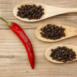 Black and red pepper in wooden spoon on the old board — Stock Photo #23321092