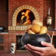 Cast iron pot with a potato in the hands in Russian cuisine  wit - Stock Photo
