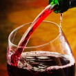 Red wine being poured into wine glass — Stock Photo #23548593