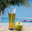 Glass of apple juice on a beach table — Stock Photo