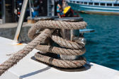Knot on a bollard of a boat. Blue sea in a background. — Stock Photo